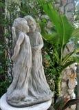 Escultura del niño pequeño y de la muchacha y vid verde en jardín inglés Imagen de archivo
