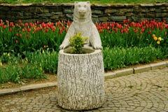 Escultura del oso con las flores en parque Imágenes de archivo libres de regalías