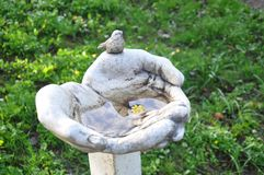 Escultura del parque, manos, pájaro, flor imagen de archivo