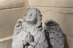 A escultura do anjo com mãos juntou-se na oração silenciosa foto de stock