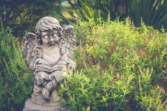 Escultura do cupido ou lugar branco da estátua no jardim exterior cercado com o natural verde para a decoração de jardinagem Fotos de Stock