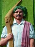 Escultura do homem indiano do trabalho agrícola, no vestido tradicional, com a guilhotina Foto de Stock Royalty Free