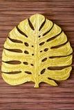 Escultura dourada da folha com fundo de madeira Fotografia de Stock Royalty Free