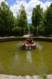 Escultura em uma fonte com anjos pequenos acima sobre os peixes que emanam a água nos jardins da exploração agrícola Art History  fotografia de stock