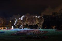 Escultura hecha de luces, vaca de la vaca de la Navidad de la flor en Ventspils, Letonia Foto de archivo