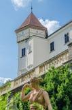 Escultura medieval rodeada por el verde delante del castillo blanco restaurado hermoso y del cielo azul en República Checa foto de archivo