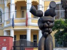 Escultura moderna de un tronco humano de la frente a un edificio neoclásico de Tirana en Albania fotos de archivo