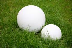 Escultura moderna del jardín - bola de dos blancos en césped de la hierba verde Foto de archivo libre de regalías