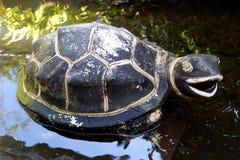 Escultura preta da tartaruga do vintage isolada na lagoa fotografia de stock