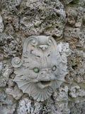 Escultura tallada piedra de la cara de los pescados en gruta de la pared de la roca Foto de archivo