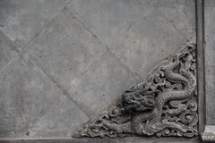 Escultura velha de um dragão na parede de pedra Imagem de Stock