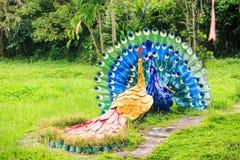 Esculturas de pavos reales en hierba por la trayectoria de piedra en parque Fotografía de archivo