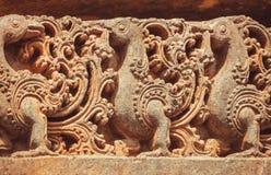 Esculturas de piedra en las paredes del templo hindú con los pavos reales míticos y los modelos diseñados La India Fotos de archivo libres de regalías