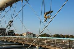 Esculturas do ferro da instalação da arte entre a água e o céu na ponte pedestre Imagem de Stock