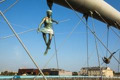 Esculturas do ferro da instalação da arte entre a água e o céu na ponte pedestre Imagens de Stock