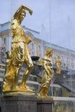 Esculturas douradas pela cascata grande das fontes em Pertergof, St Petersburg Fotos de Stock