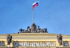 Esculturas y la bandera rusa en el edificio del sínodo y del senado, St Petersburg fotos de archivo libres de regalías