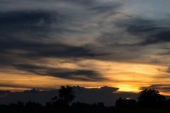 Escuridão e por do sol sobre o campo fotografia de stock