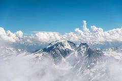 Escuro - céu azul com as nuvens nos picos rochosos das montanhas cobertas com as geleiras e a neve Fotografia de Stock Royalty Free