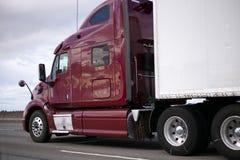Escuro - do equipamento caminhão grande profissional vermelho semi com o reboque no roa Imagem de Stock Royalty Free