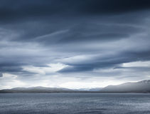 Escuro - nuvens tormentosos azuis sobre as rochas litorais fotos de stock