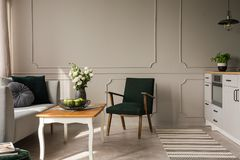 Escuro retro - poltrona verde ao lado da mesa de centro de madeira com maçãs e rosas no vaso no interior da cozinha e da sala de  imagens de stock royalty free