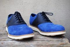 Escuro - sapatilhas azuis com uma sola branca em um fundo de madeira imagens de stock royalty free