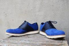 Escuro - sapatilhas azuis com uma sola branca em um fundo de madeira fotos de stock