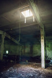 Escuros grandes esvaziam a sala abandonada do armazém com a janela no teto e iluminam-se dele Foto de Stock