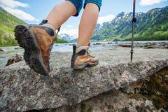 Escursione del primo piano dello stivale sulle rocce della montagna fotografie stock libere da diritti