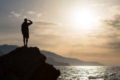 Escursione del viaggiatore con zaino e sacco a pelo della siluetta, uomo che esamina oceano Fotografia Stock Libera da Diritti