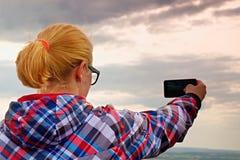 Escursione della donna bionda dei capelli lunghi che prende foto con lo Smart Phone alle montagne fotografie stock libere da diritti