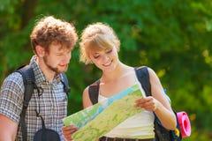 Escursione della mappa backpacking della lettura delle coppie sul viaggio Immagini Stock Libere da Diritti