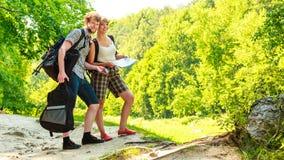 Escursione della mappa backpacking della lettura delle coppie sul viaggio Fotografie Stock Libere da Diritti