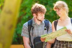 Escursione della mappa backpacking della lettura delle coppie sul viaggio Fotografia Stock Libera da Diritti
