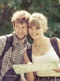 Escursione della mappa backpacking della lettura delle coppie sul viaggio Immagini Stock