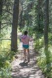 Escursione della ragazza che cammina nella foresta fotografia stock