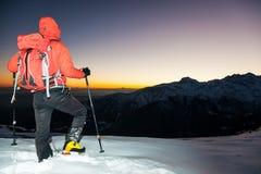 Escursione di inverno: l'uomo sta su una cresta nevosa che esamina il tramonto Fotografia Stock
