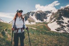 Escursione di viaggio di viaggiatore con zaino e sacco a pelo della donna in montagne Immagini Stock