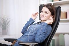 Escuta de assento da mulher de negócios satisfeita a música fotografia de stock