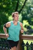 Escuta de corrida do corredor a música app no parque da cidade fotos de stock royalty free