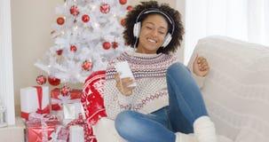 Escuta de relaxamento da moça a música do Natal foto de stock