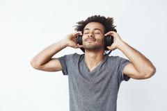Escuta de sorriso do homem africano feliz a música nos fones de ouvido Olhos fechados imagens de stock royalty free