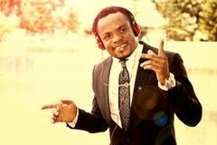 Escuta exterior do homem de negócios a música com fones de ouvido Fotografia de Stock Royalty Free