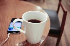 Escuta a música em um smartphone ao beber o café apenas em um café foto de stock royalty free