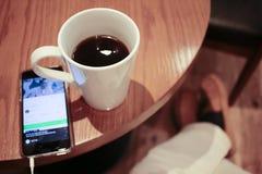 Escuta a música em um smartphone ao beber o café apenas em um café foto de stock