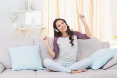 Escuta moreno bonita a música no sofá Imagem de Stock Royalty Free