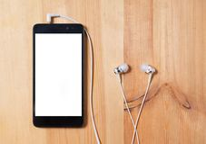 Escute a m?sica smartphone vertical com caixa preta e uma tela branca vazia e fones de ouvido com uma orelha na superfície de mad fotos de stock royalty free
