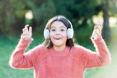 Escute no estilo Fones de ouvido vestindo da criança da menina A criança feliz aprecia escutar a música no vai Pequeno adorável imagem de stock royalty free