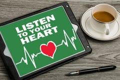 escute seu coração no tela táctil imagens de stock